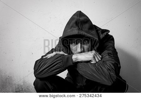 Homeless Man Drug And Alcohol Addict Sitting Alone And Depressed On The Street In Winter Clothes Fee