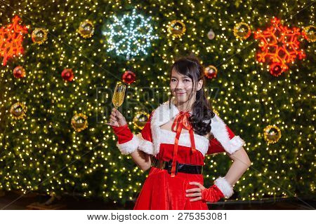 Happy Smiling Santa Girl Is Cute In Red Suit And Hand Holding Champagne With Christmas Tree Backgrou