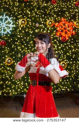 Happy Smiling Santa Girl Is Cute In Red Suit And Hand Love Heart With Christmas Tree Background Cele