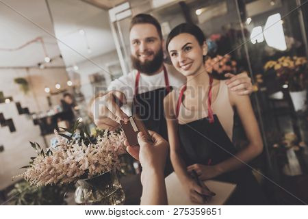The Girl Pays To Buy A Bouquet Of Flowers Florist. A Young Girl Pays For The Purchase Of A Bouquet O