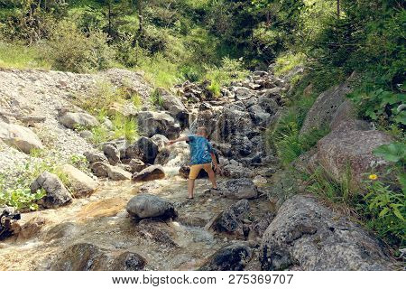 The Child Sits By The Brook On The Rocks In Nature.
