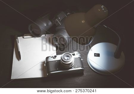 Blank page with copy space, pen, binoculars and photo camera on a black spy agent or paparazzi photograph table background. Interrogation. Surveillance concept. poster