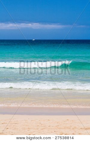 waves rolling onto a Fuerteventura beach, small white boat in background