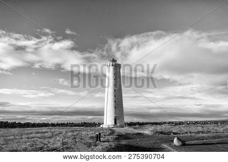 Lighthouse In Reykjavik, Iceland. Lighthouse Tower In Autumn Field On Cloudy Blue Sky. Structure And