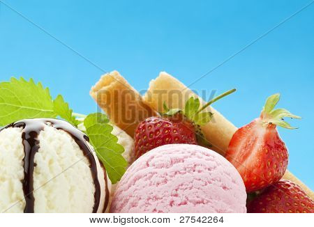 closeup of ice cream scoops with strawberries, waffles and chocolate topping against vibrant blue background, copy space in upper half