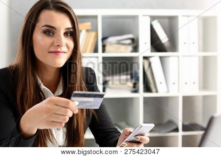 Businesswoman In The Office Holds A Plastic Credit Debit Card In Her Hand Portrait. Makes Online Pur