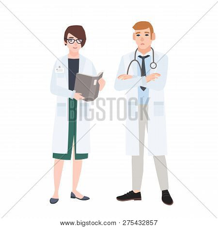 Male And Female Doctors Wearing White Coats Talking To Each Other. Conversation Or Discussion Betwee