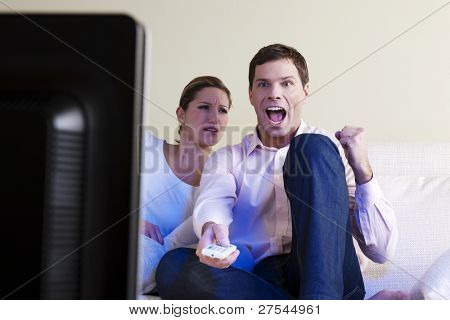 Man exulting watching tv, woman disappointed