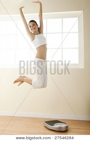 Excited young woman jumping, weight scale on the floor.