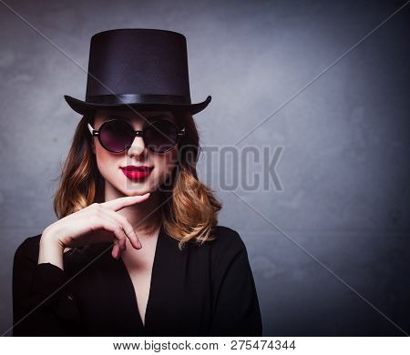 Style And Mystique Redhead Girl In Top Hat And Sunglasses On Grey Background