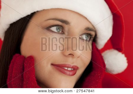 Close-up of a beautiful woman in santa's hat, on red background