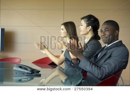 Business team applauding while at a meeting poster