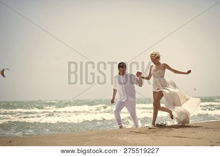 Beautiful Laughing Young Wedding Couple Of Man And Woman In White Running Along Ocean Beach Shore On