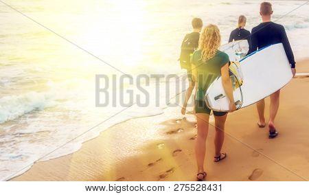 Boys And Bikini Girl Teen Surfers Running Jumping On Surfboards At The Beach