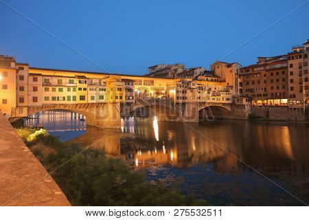 FLORENCE, ITALY - AUGUST 9, 2018: Night view to Ponte Vecchio across Arno river in Florence. The historical center of Florence is listed as UNESCO World Heritage since 1982