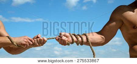 Pulling Rope. Male Hands Pull Opposite Ends Of Rope. Tug War Is A Sport. Test Of Muscular Strength.