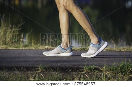 The Female Walking At The Morning For Warm Up Body For Jogging And Exercise.