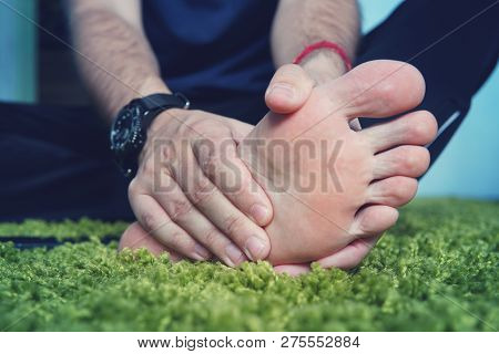 Man With Painful And Inflamed Gout On His Foot Around The Big Toe Area. Mans Hand Being Massaged A F