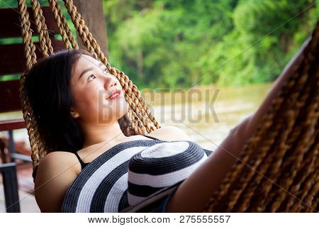 Asian Women With A Vintage Hat Is Resting On A Hammock Beside The Jungle Lake And Looking Outside.