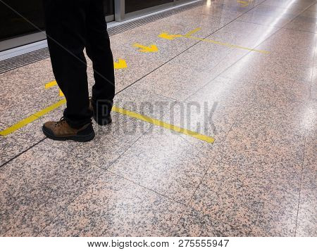 Man Standing In Front Of The Rail Door And Yellow Arrow Sign.