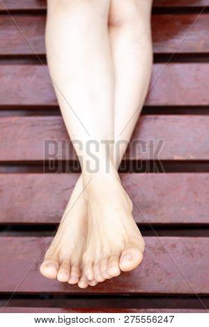 Asian Women Feet On Wooden Bed Close Up.