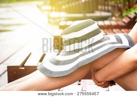 Women Relaxing On A Wooden Flat Bed Near The River With A Big Vintage Hat On Her Legs. Process In Vi