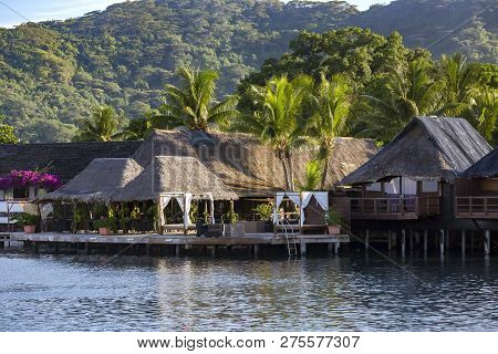 Luxury Overwater Thatched Roof Bungalow Resort On A Wooden Pontoon In The Clear Blue Lagoon On Bora