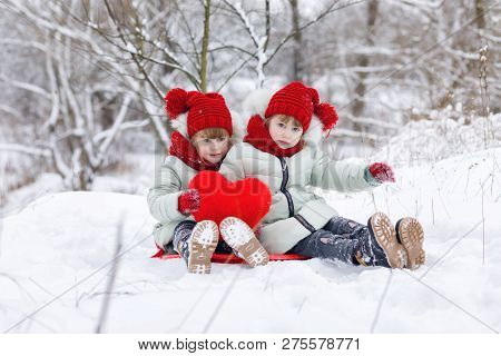Funny Sisters Twins Are Sitting On The Snowy Ground And Holding A Huge Red Heart In Their Hands Duri