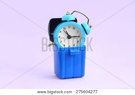 Wasting Time Concept. Alarm Clock In Trash Bin