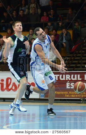 KAPOSVAR, HUNGARY - DECEMBER 10: Balazs Szoke (in white) in action at a Hungarian Championship basketball game Kaposvar (white) vs. Szeged (blue) on December 10, 2011 in Kaposvar, Hungary.