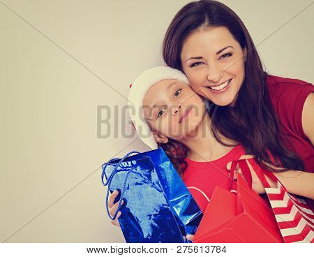 Happy Laughing Mother Hugging With Love Her Cute Daughter In Santa Clause Hat And Holding Christmas