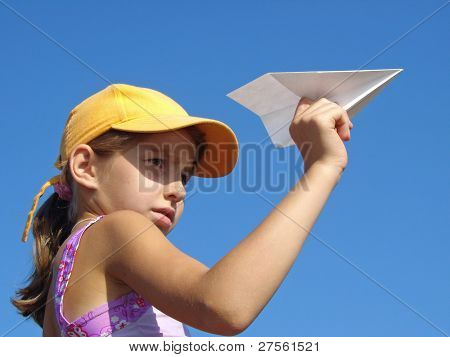 young girl with paper plane against blue sky