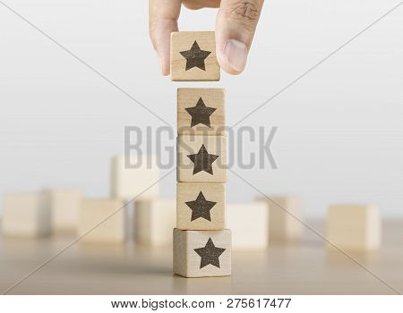Hand Arranging Wooden Blocks With The Five Star Symbol. The Best Rating, The Best Ranking, The Best