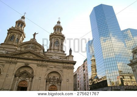 Metropolitan Cathedral of Santiago reflected in the glass clad facade of the modern building, Plaza de Armas the mainsquare of Santiago City, Chile poster