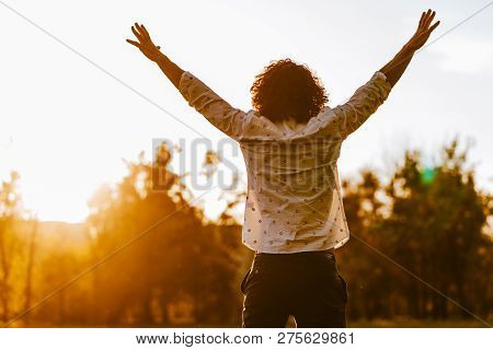 Rear View Shot Of Happy Young Man Rising Hands Up Standing In The Park Enjoying Beautiful Sunset Vie
