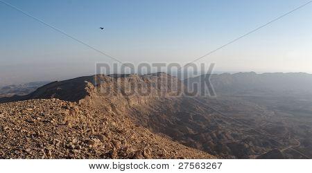 Rim of desert canyon at sunset
