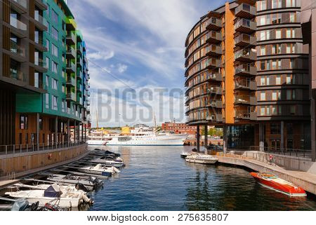 OSLO, NORWAY - JULY 23, 2018: Modern scandinavian architecture at renovated Tjuvholmen waterfront district. HNoMY Norge Royal Yacht of the King of Norway is seen in background