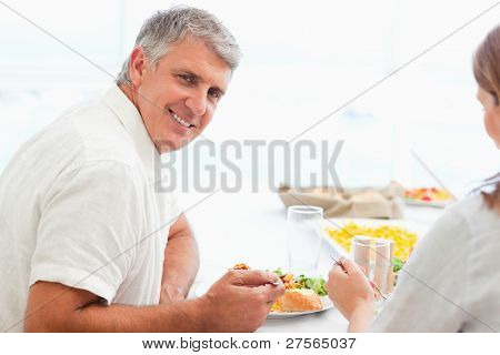 Side view of happy smiling mature man during dinner
