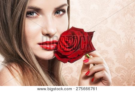 Beautiful young woman with red rose on beige background