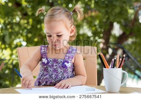 Happy Smiling Baby Girl Drawing Pictures Outdoors In Garden In Summer Time