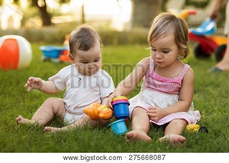 Happy Smiling Baby Brother And Toddler Sister Playing With Toys Togerther In Backyard Garden In Summ