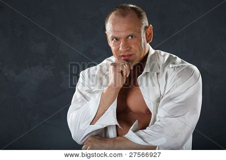 Tanned bodybuilder wearing white wet shirt looks thoughtfully at camera.