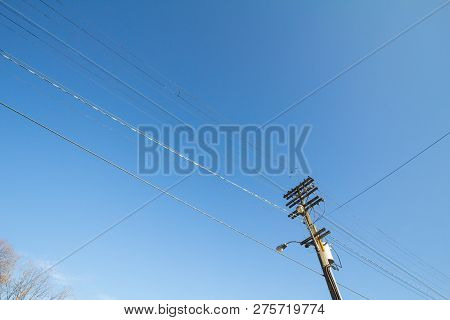 Electric And Telephone Power Line, Old And Outdated, On A Rotten Wooden Pole, Abiding By North Ameri