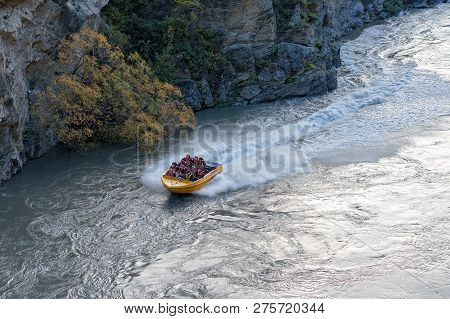 Shotover River, New Zealand: Tourists Enjoying Exciting Jet Boat Ride Through The Spectacular Canyon