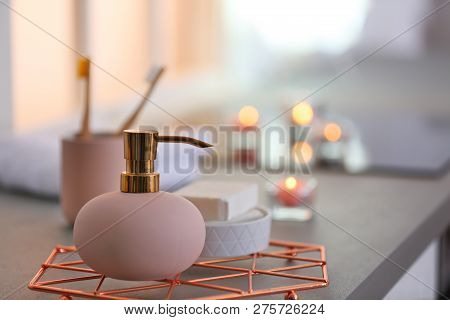 Bottle with liquid soap and toiletries on table against blurred background. Space for text poster