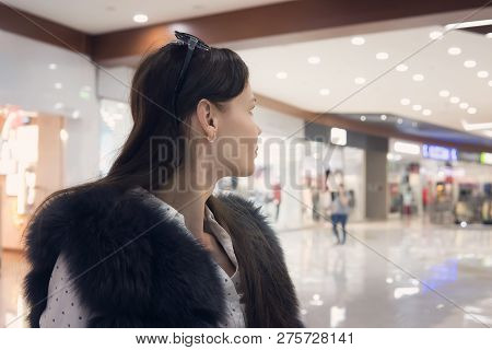 Close Up Of A Young Brunet Girl In Shopping Mall Looking Away From The Camera. Good-looking Woman St