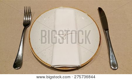 Top View Of Prepared Empty Table Set With White Plate And Silverware With White Clean Wrapped Checke