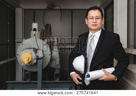 Asian Executive Engineer Stand Beside Heavy Machinery In Industrial Factory, He Holds White Helmet I