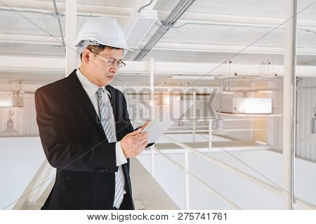 Asian Executive Engineer In White Helmet Using Tablet In Industrial Factory, Concept For Executive E