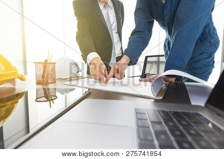 Businessman In Suit And Engineer In Coverall Cloth Taking And Reviewing Plan Design In Modern Office